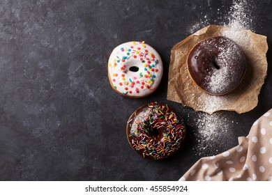 Colorful donuts on stone table. Top view with copy space