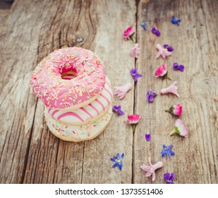 Colorful donuts on a wooden background. Party food concept