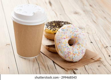 Colorful donuts and paper cup on wooden table, close up