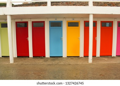 colorful doors of changing rooms next to a beach