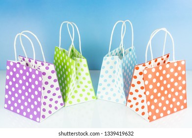 Colorful dotted bags for gifts, blue background