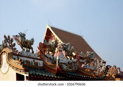 Colorful dragon headed unicorn or qilin on a shrine roof blue sky background