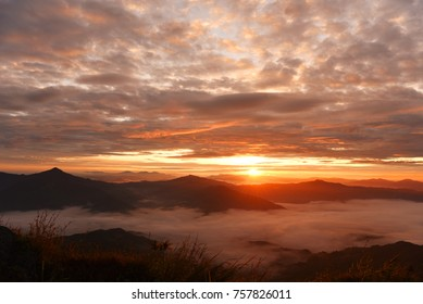 colorful dramatic sky with clouds - foggy landscape and mountains
