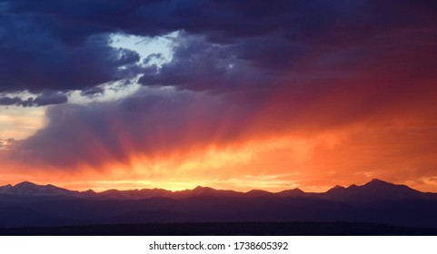 colorful ,dramatic sunset and dark clouds over long's peak and the front range of the colorado rocky mountains, as seen from broomfield, colorado