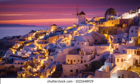 Colorful and Dramatic Sunset with Night Lights in Mediterranean Town of Oia, Santorini, Greece, Europe