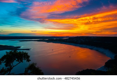 Colorful Dramatic Sunset Over Lake Travis golden and purple reflecting off water around the cove of high limestone cliffs outside of Austin , Texas Hill Country