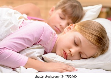 Colorful dreams. Pleasant content little sisters lying in bed and sleeping