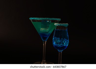 Colorful drink in a cocktail glass, with ice cubes, summer drink, party night