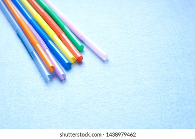 Colorful drinking straws on a blue background.