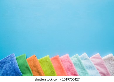 Colorful, dry microfiber cloths for different surfaces cleaning in kitchen, bathroom and other rooms. Empty place for text or logo on blue background. Cleaning service concept. Regular clean up.