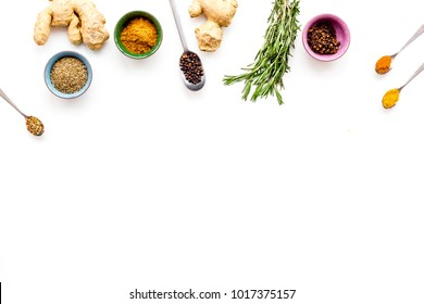 Colorful dry spices in bowls and spoons near ginger and rosemary on white background top view copy space