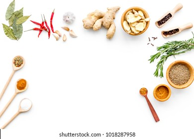 Colorful dry spices in bowls and spoons near ginger, garlic, rosemary on white background top view copy space