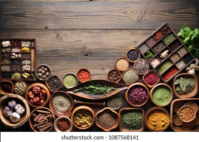 Colorful dry spices and legume plants in bowls. Rustic wooden kitchen table. Top view.