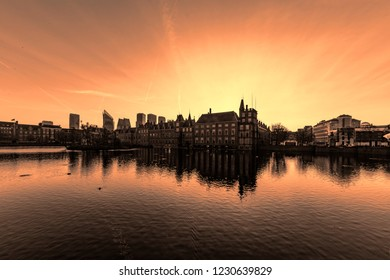 Colorful Dutch Parliament, Hofvijver in Dutch, reflected on the water of the canal at the early freezing sunrise in The Hague, Netherlands