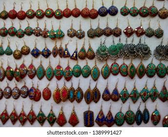 Colorful earrings(Jhumkas) for sale at shop in Delhi/Dilli Haat (INA) market.Indian women's metallic jewellery.