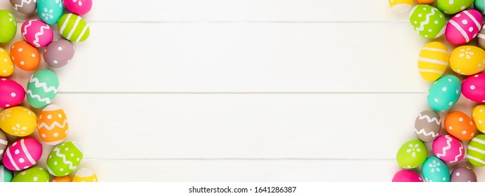 Colorful Easter banner with double Easter Egg side border against a white wood background. Above view with copy space.