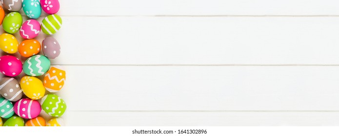 Colorful Easter banner with side border of Easter Eggs against a white wood background. Above view with copy space.