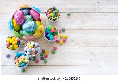 Colorful Easter candies on a rustic wood white background