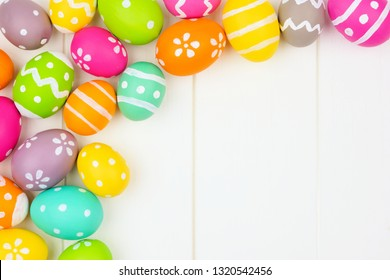 Colorful Easter Egg corner border against a white wood background. Top view with copy space.