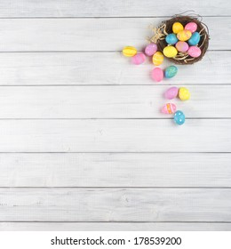 Colorful Easter Egg Nest Overflowing from Up Above with Extra White or Gray Wood Board Background for room or space for copy, text, words.  A flat lay with square crop