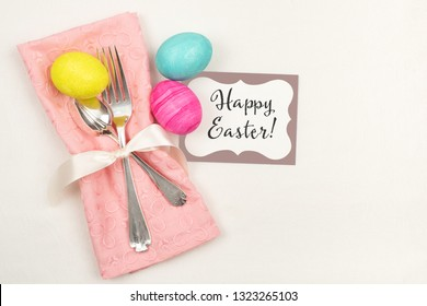 Colorful Easter Egg Table Setting with Silverware, Dyed eggs, Pink Napkin, Card on off white cloth with room or space for copy, text or your words.  Horizontal with a flat layout with above view