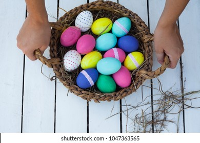 Colorful easter eggs in basket on wooden table. Top view.