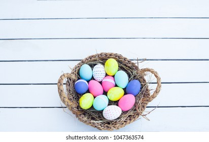 Colorful easter eggs in basket on wooden table. Top view with copy space