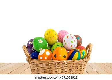 Colorful Easter eggs in a basket on wood texture isolated on white background.
