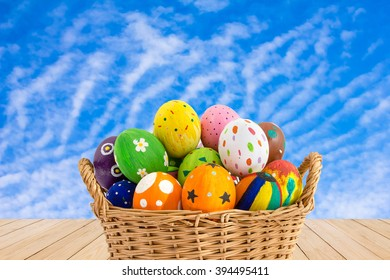 Colorful Easter eggs in a basket on wood texture on blue sky background.