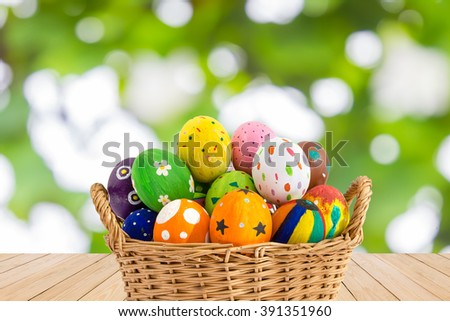 Colorful Easter eggs in a basket on wood texture on green bokeh background.