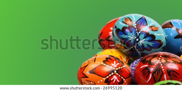 Colorful Easter Eggs in Basket on green background