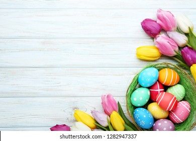 Colorful easter eggs in basket with tulips on wooden table