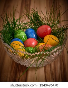 Colorful easter eggs in a bed of grass in a crystal tube on a background of walnut. Dark vignette