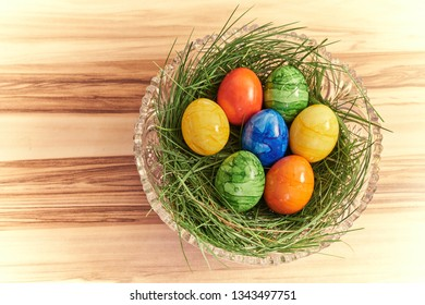 Colorful easter eggs in a bed of grass in a crystal tube on a background of walnut. Bright vignette.