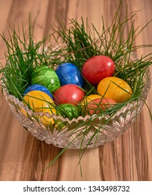 Colorful easter eggs in a bed of grass in a crystal shell on a background of walnut.