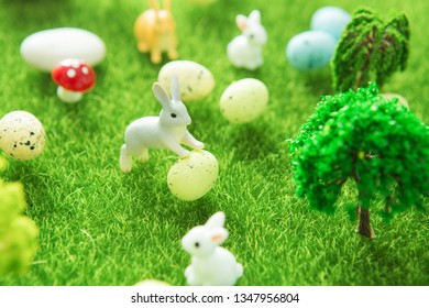 Colorful easter eggs and a big yellow easter egg on spring green grass.