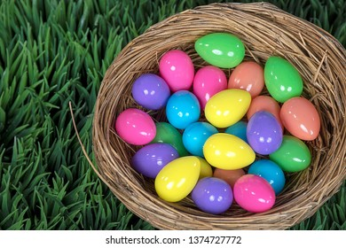 colorful Easter eggs in bird nest on green grass