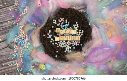 Colorful Easter eggs in bird nest surrounded with pastel colored feathers and wooden cubes with the text Happy Easter top view, modern background design, Easter holliday, Spring, concept greeting card