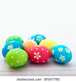 Colorful easter eggs and branch with pattern flowers. Top view, square. Poster, mock up for design. Selective focus