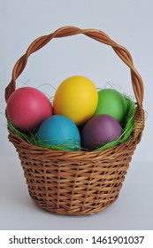 Colorful Easter eggs in a brown basket, white background