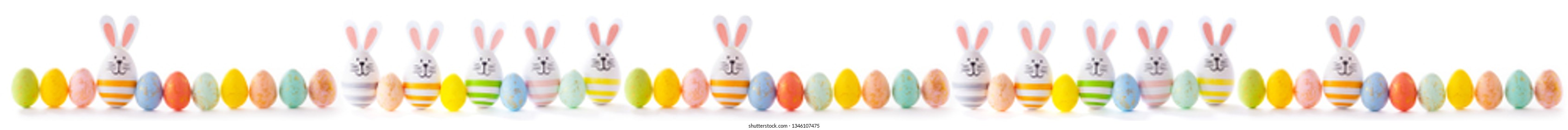 colorful  easter eggs with bunny ears and funny face panorama isolated on white background
