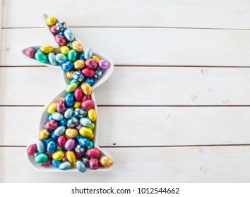 Colorful easter eggs in bunny tray on wooden background