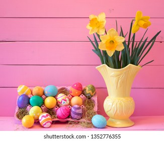 Colorful Easter Eggs in Carton with Vintage Yellow Vase filled with Spring Daffodils against Bright Pink Wood Board Background with space for copy, text or words.  Horizontal