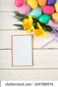 Colorful Easter Eggs and Daffodil Flowers still life on Rustic White Board Background with blank menu card with room or space for copy, text, or words. Vertical photo from above with looking down view