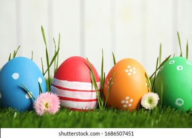 Colorful Easter eggs and daisy flowers in green grass against white background, closeup