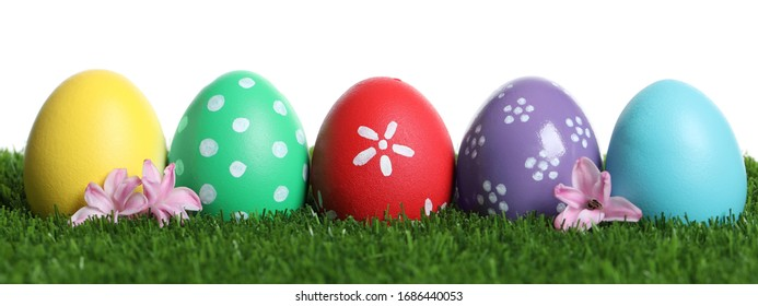 Colorful Easter eggs and flowers on green grass against white background