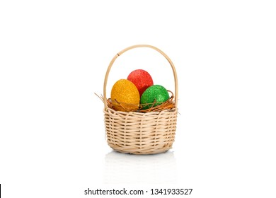 Colorful easter eggs with glitter in the nest on wooden basket isolated over white background. Happy Easter