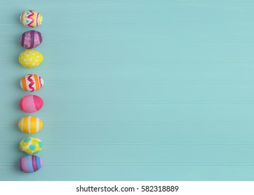 Colorful Easter Eggs in a line on side of a Teal Blue Beadboard Wood Background with extra, blank room or space for copy, text, or your words.  It's horizontal and perfect for a card or party invite