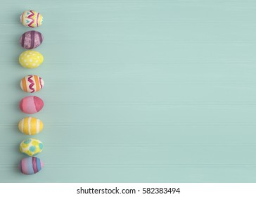 Colorful Easter Eggs in a line on side of Teal Blue Beadboard Wood Background with extra, blank room or space for copy, text, or your words.  It's horizontal with faded sepia toned, filter processing