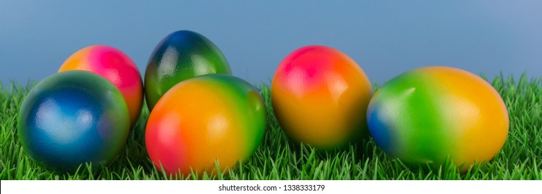 Colorful Easter eggs in a meadow, banner